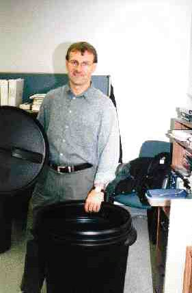 A custom-built automation system helps Scepter cost-effectively trim a two-inch section from the top of this blow molded garbage can. Plant manager Don Villers (above) says he doesn't think it would have been feasible to manufacture the can without the automation.