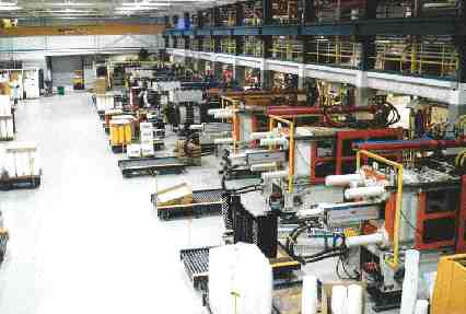 Molding presses at Ropak are arranged in two parallel rows, with a wide central corridor to give the automated guided vehicle room to pick up pallets of completed pails. Loaders, blenders and gaylords are all grouped in the mezzanine above.