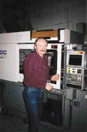 Bruce Borstmayer, pictured running the company's new 143-ton Sumitomo press, says the machine will initially be used to mold a polycarbonate lens and polypropylene test tubes.