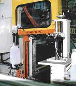 Beside the machine, an upper set of grippers executes a 90 degree turn to transfer the bottle to an indexing fixture.