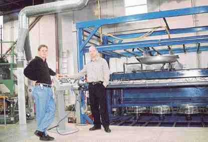 Roy Ford and Mark Oribine at the controls of Custom Vacform's latest acquisition, a 6 ft. x 11 ft. vacuum former that will allow the company to pursue contracts for large parts and offer an alternative to FRP products.