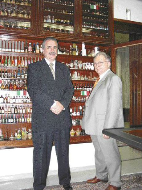 Global business, global collection: In the Plasticos Mueller board room, Sangali and Jacob examine Jacob's collection of miniature liquor bottles.