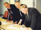 Ted Callighen (left) of CAMM, Les Payne (centre) representing CPMA, and Ed Glover of CTMA sign the documents to form a national organization.