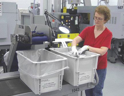 An operator at the Vienna plant applies labels and prepares a container of components for pick-up by an automated guided vehicle. Each container gets a unique tracking label. The serial number and destination are established before it even leaves the press.