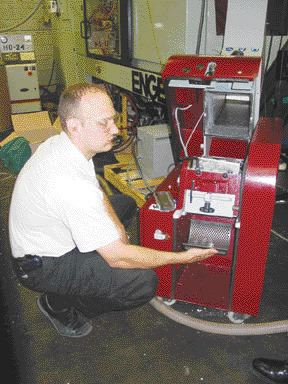 Christian Weiss, Wittmann product manager at Nucon Wittmann Inc., displays the inside of a compact, beside the press granulator at Ipex Inc.