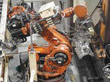 A robot takes the tin bismuth core and places it into the injection molding machine.