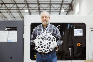 GE worker holds up a finished product in front of a polymer 3D printer at GE`s CATA facility.