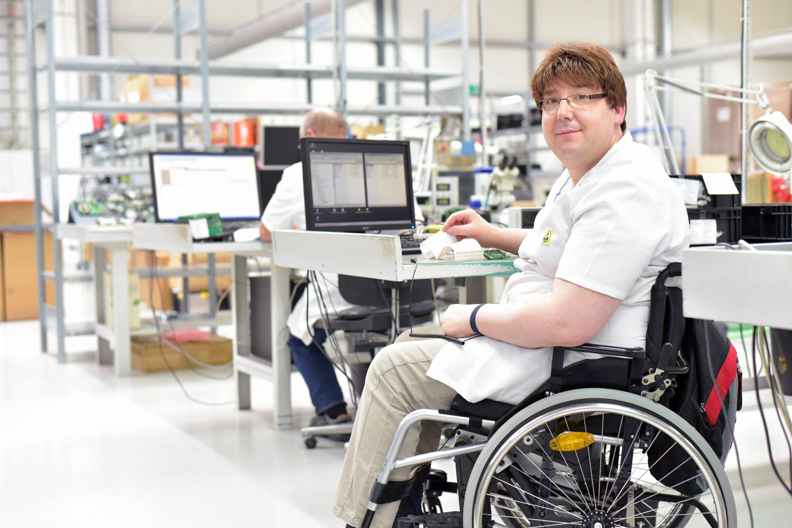 Rollstuhlfahrer am Arbeitsplatz in einer Fabrik zur Montage von Elektronik – Alltag mit Gehbehinderung // Wheelchair driver at the workplace in the industry